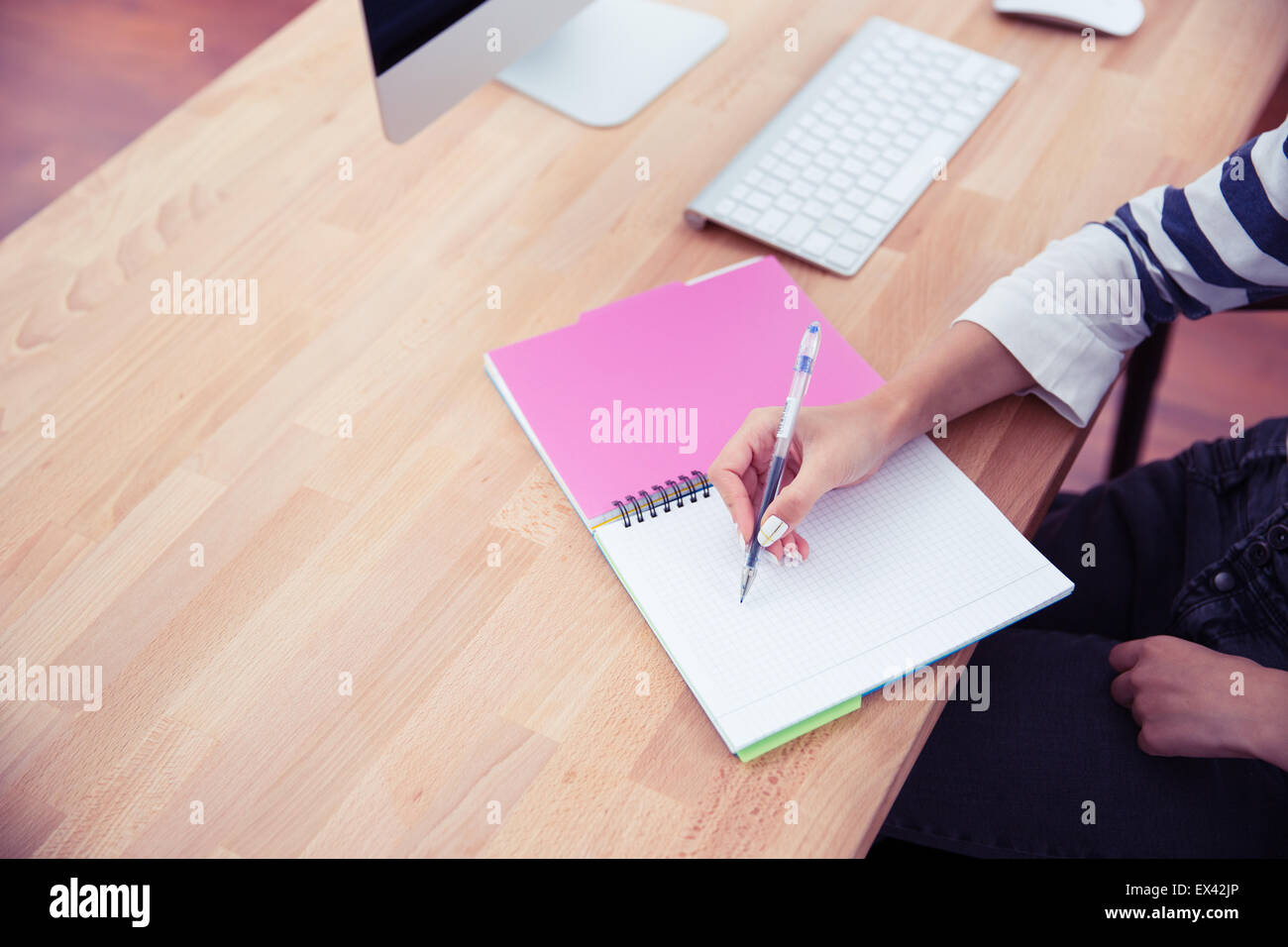 Closeup portrait of a girl writing notes in office - Stock Image