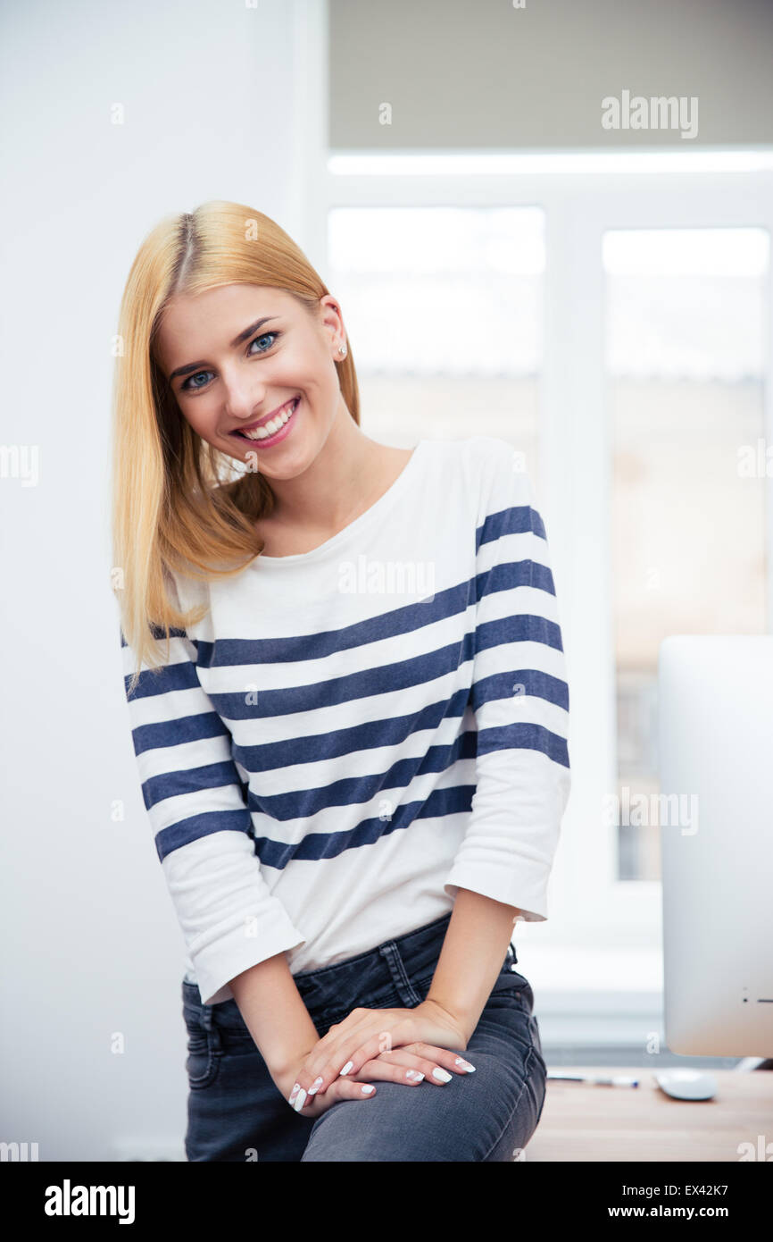 Happy young woman sitting on the table in office - Stock Image
