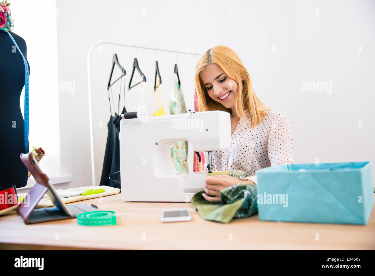Happy female tailor using sewing machine in laundry - Stock Image