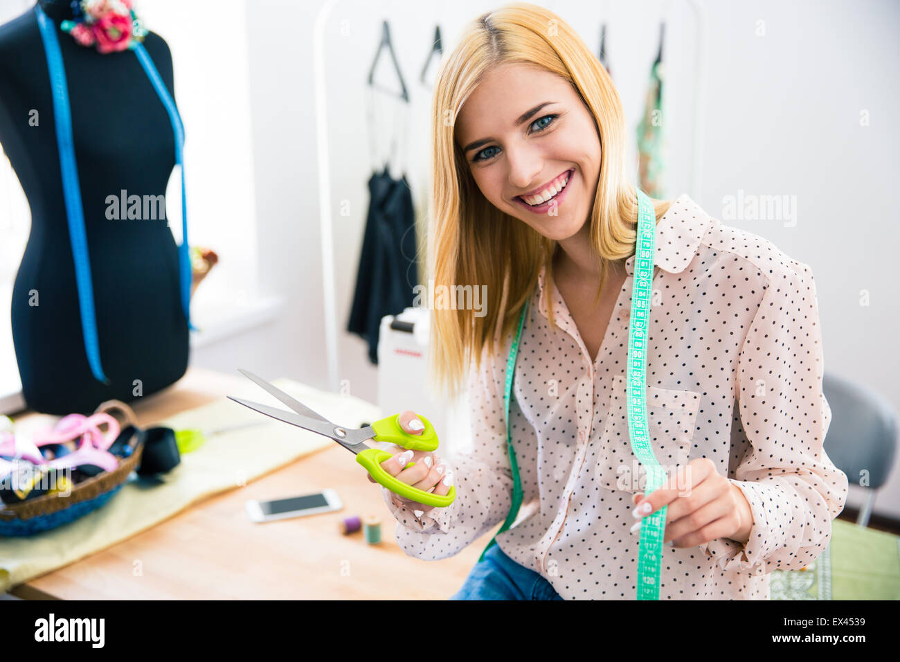 Happy female tailor standing in workshop - Stock Image