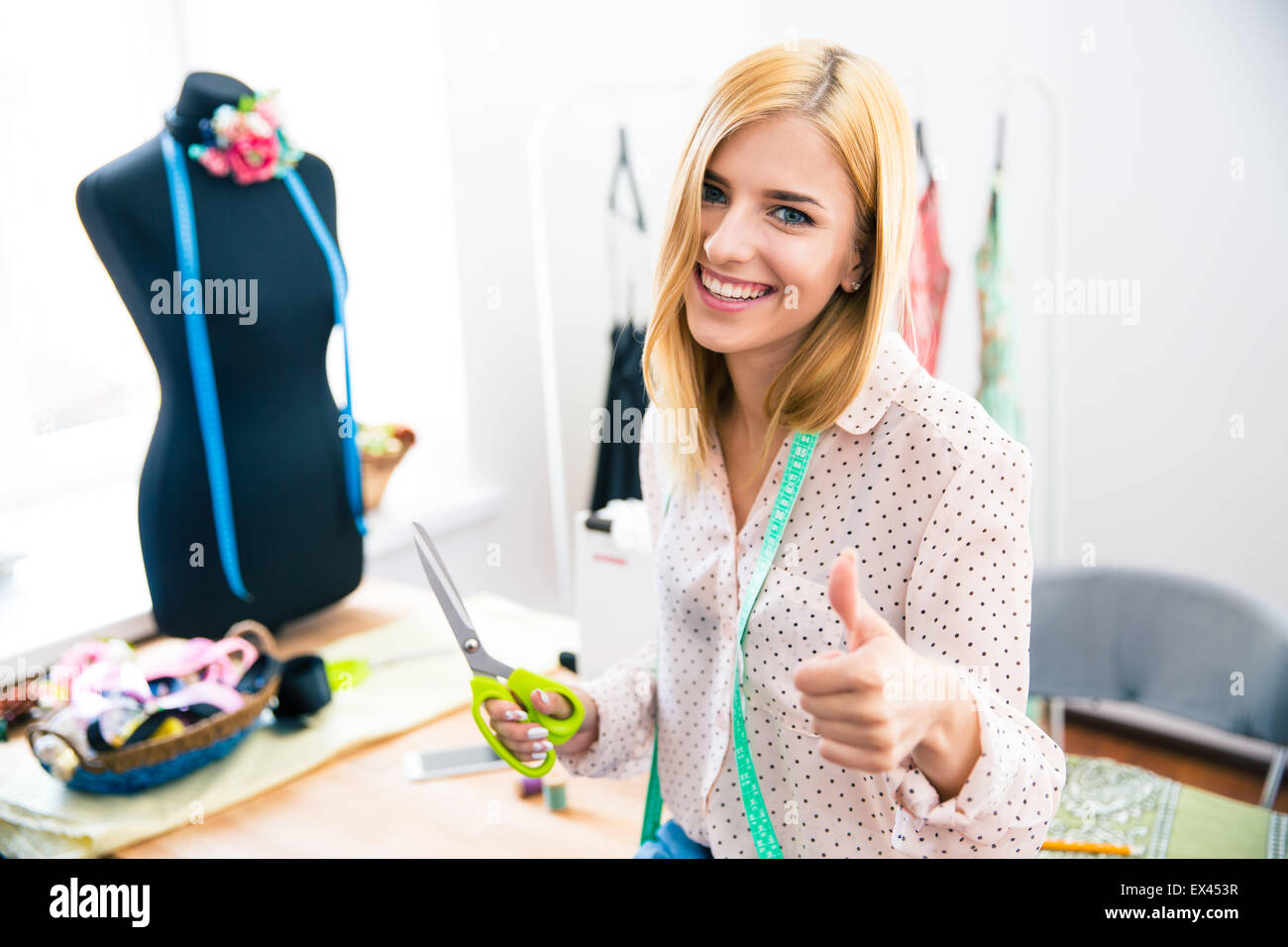 Smiling female tailor standing in workshop and showing thumb up - Stock Image
