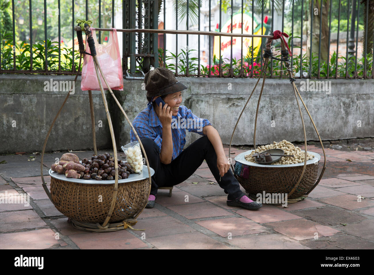 Hanoi Vietnam woman sells chestnuts while talking on her mobile phone just outside the Temple of Literature - Stock Image