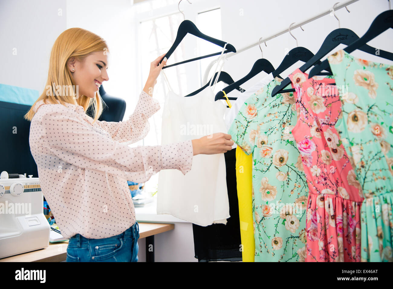 Smiling fashion designer looking on dresses in workshop - Stock Image
