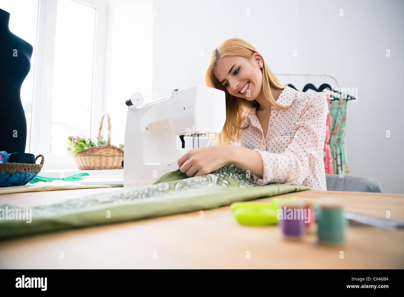Happy fashion designer working on sewing machine - Stock Image