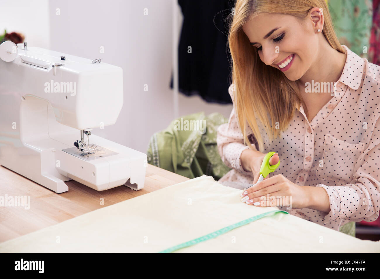 Happy female designer cutting cloth in workshop - Stock Image