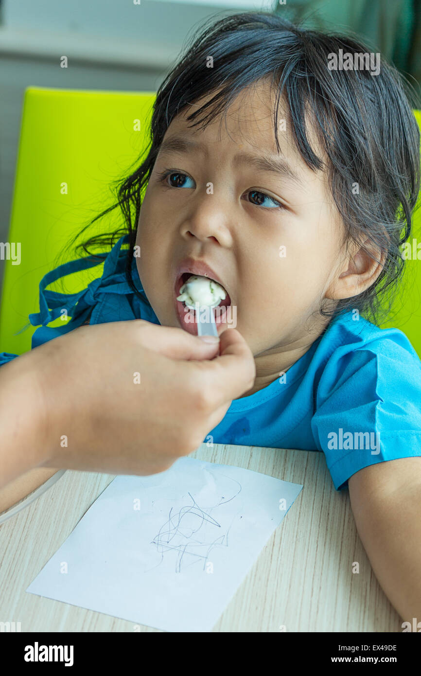 Illness asian kids eating cereal, saline intravenous (IV) on hand - Stock Image