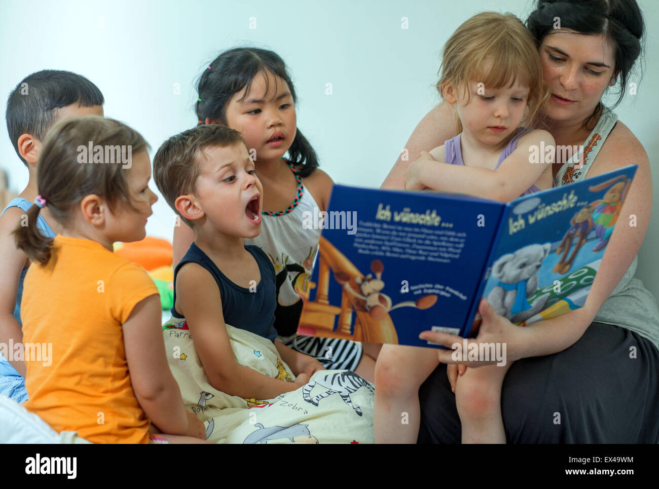 Schwerin, Germany. 06th July, 2015. Pre-school teacher Catherina Meyer reads a story to the children Lea Sophie - Stock Image