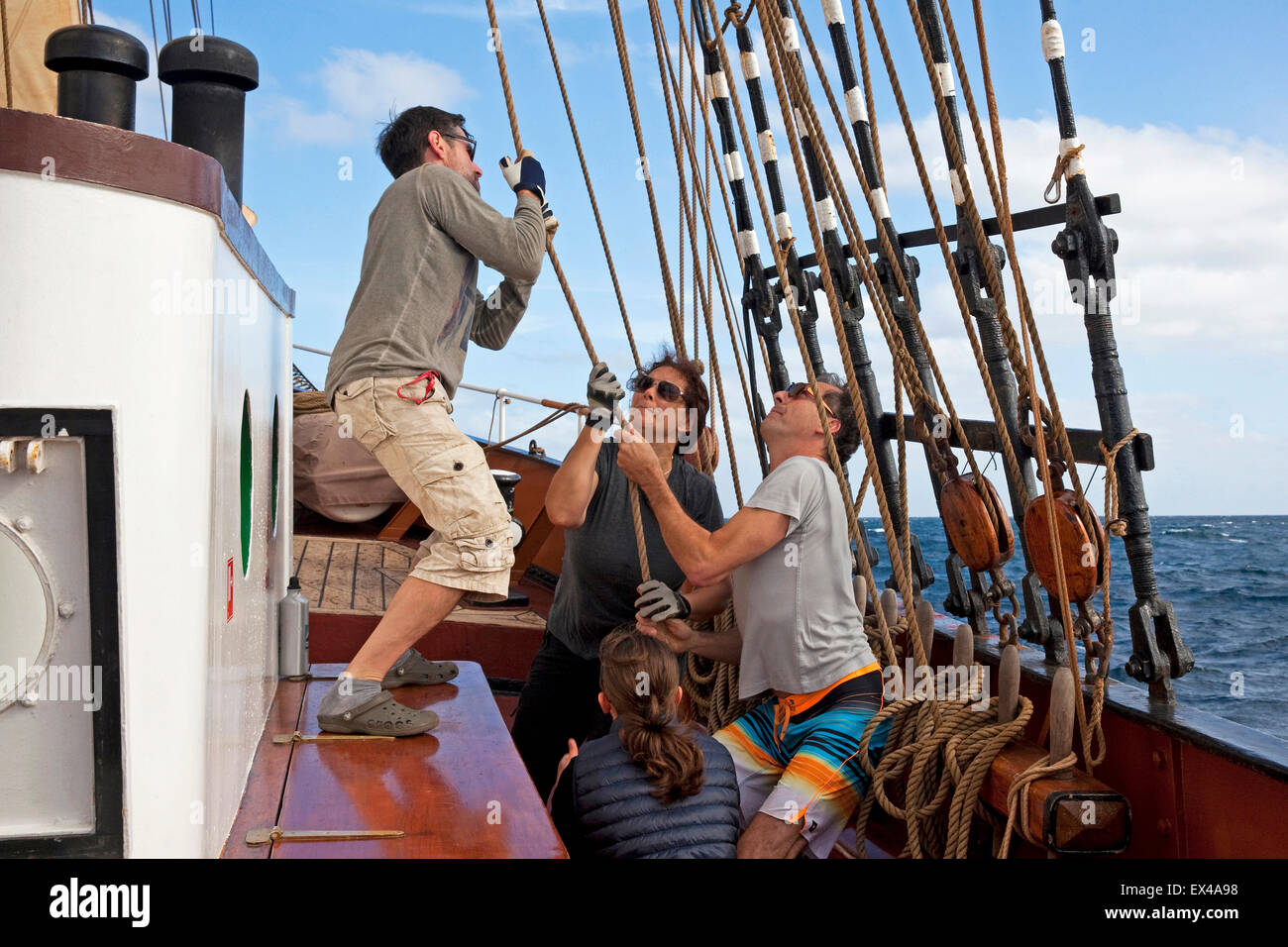 Sailors setting sail on board of the Oosterschelde, three-masted topsail schooner sailing the Atlantic Ocean near - Stock Image