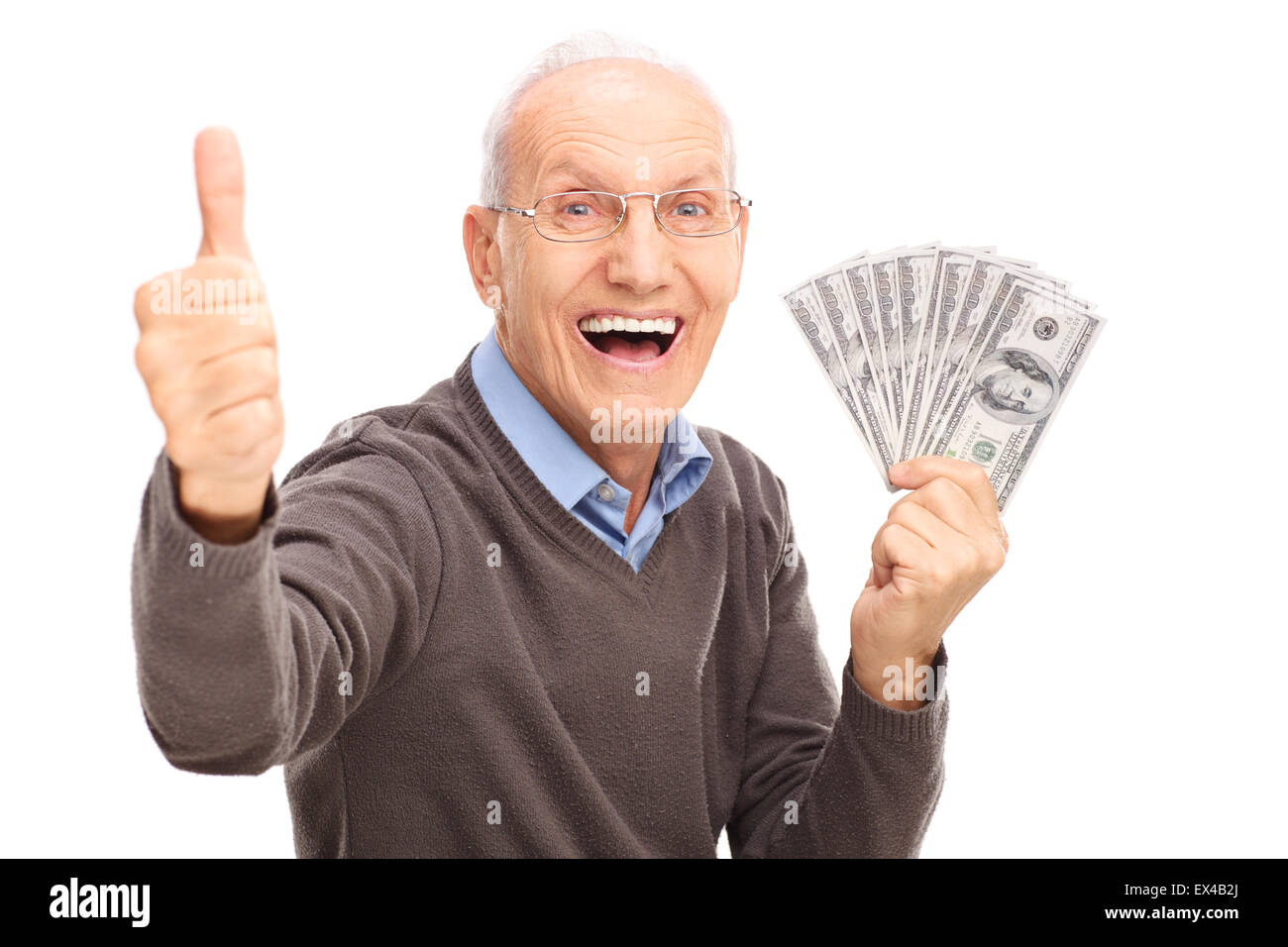 Excited senior gentleman holding a stack of money and giving a thumb up isolated on white background - Stock Image