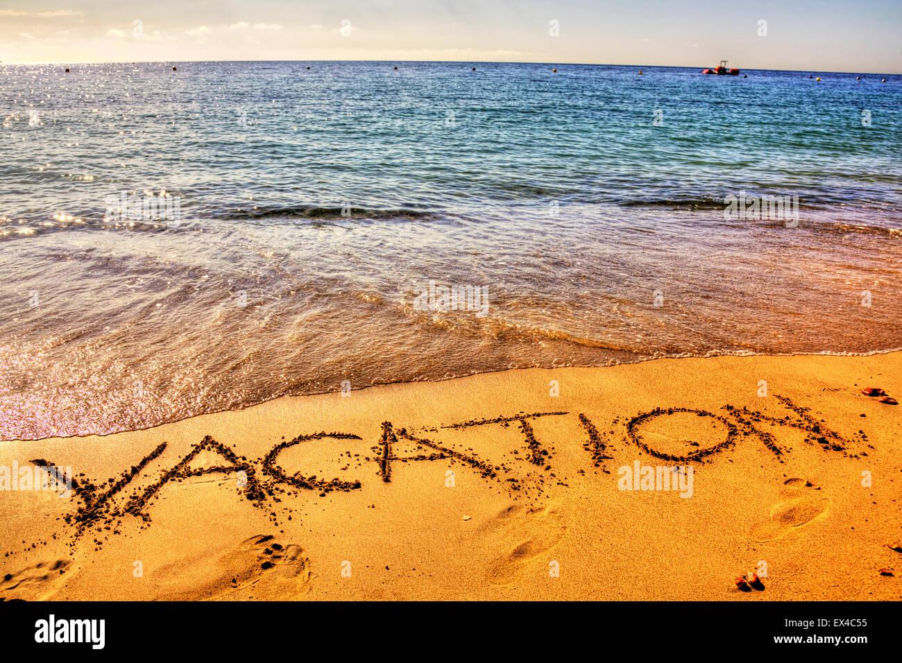 Vacation holiday word in sand written on beach resort sea coast coastline holidays vacations trips trip getaway - Stock Image