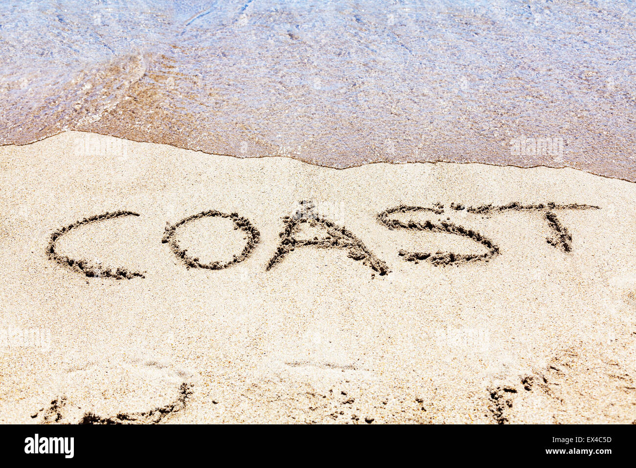 coast coastline coastal word in sand written on beach sea fun resort seas coastlines holidays vacations trips trip - Stock Image