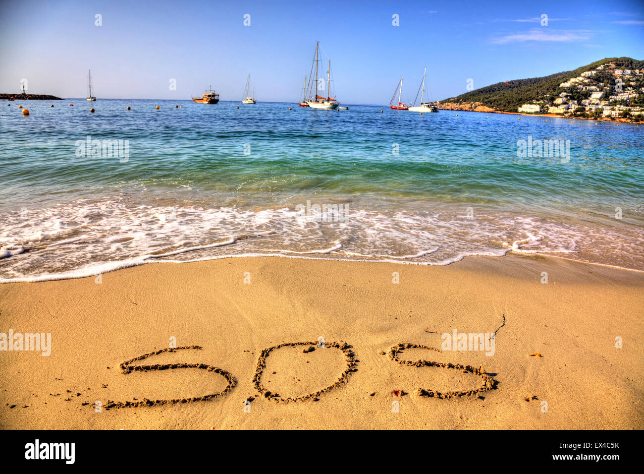 SOS save our souls rescue word in sand written on deserted beach island shipwrecked lost alone resort seas coast - Stock Image