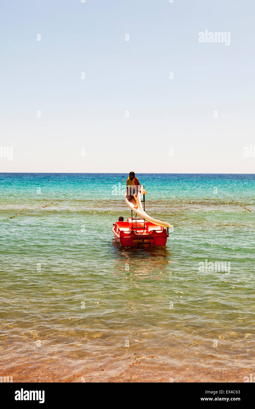 Young girl on water slide in sea life jacket vest on wearing going down waterslide Stock Photo