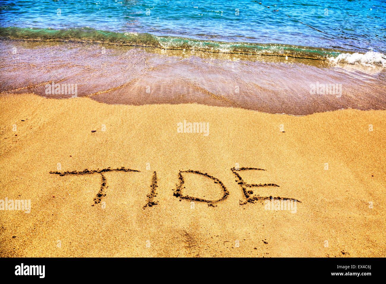 Tide tidal seas oceans word in sand sea ocean line mark written on beach resort sea coast coastline holiday getaway - Stock Image
