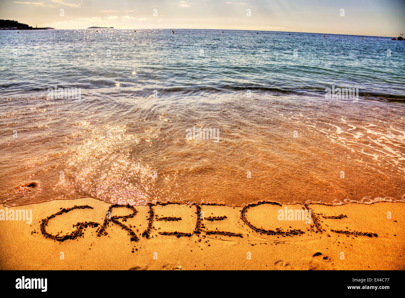 Greece Greek coast coastline metaphor sinking in debt drowning under water word written in sand sea seas coastline - Stock Image