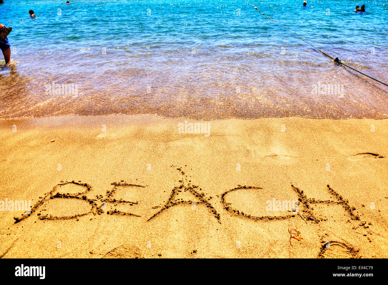 Beach word in sand written on beaches Spanish fun resort seas coast coastlines holidays vacations trips trip getaway - Stock Image