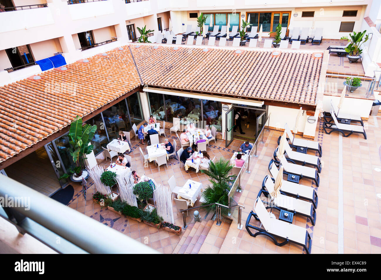 Hotel dining al fresco outside eating area diners sat at tables for lunch - Stock Image