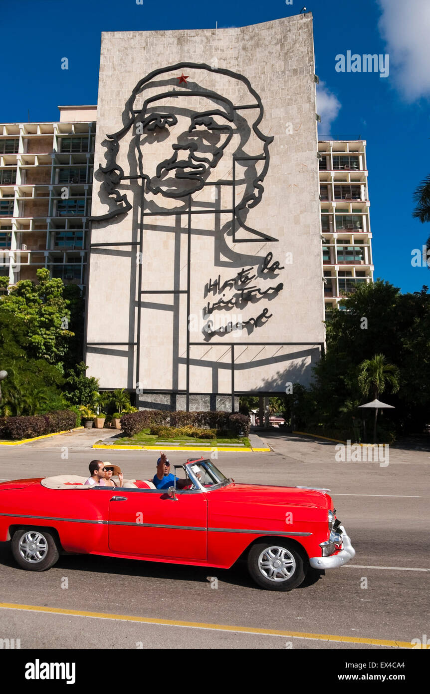 Vertical view of tourists driving by the Che Guevara mural in a vintage old car in Havana, Cuba. - Stock Image