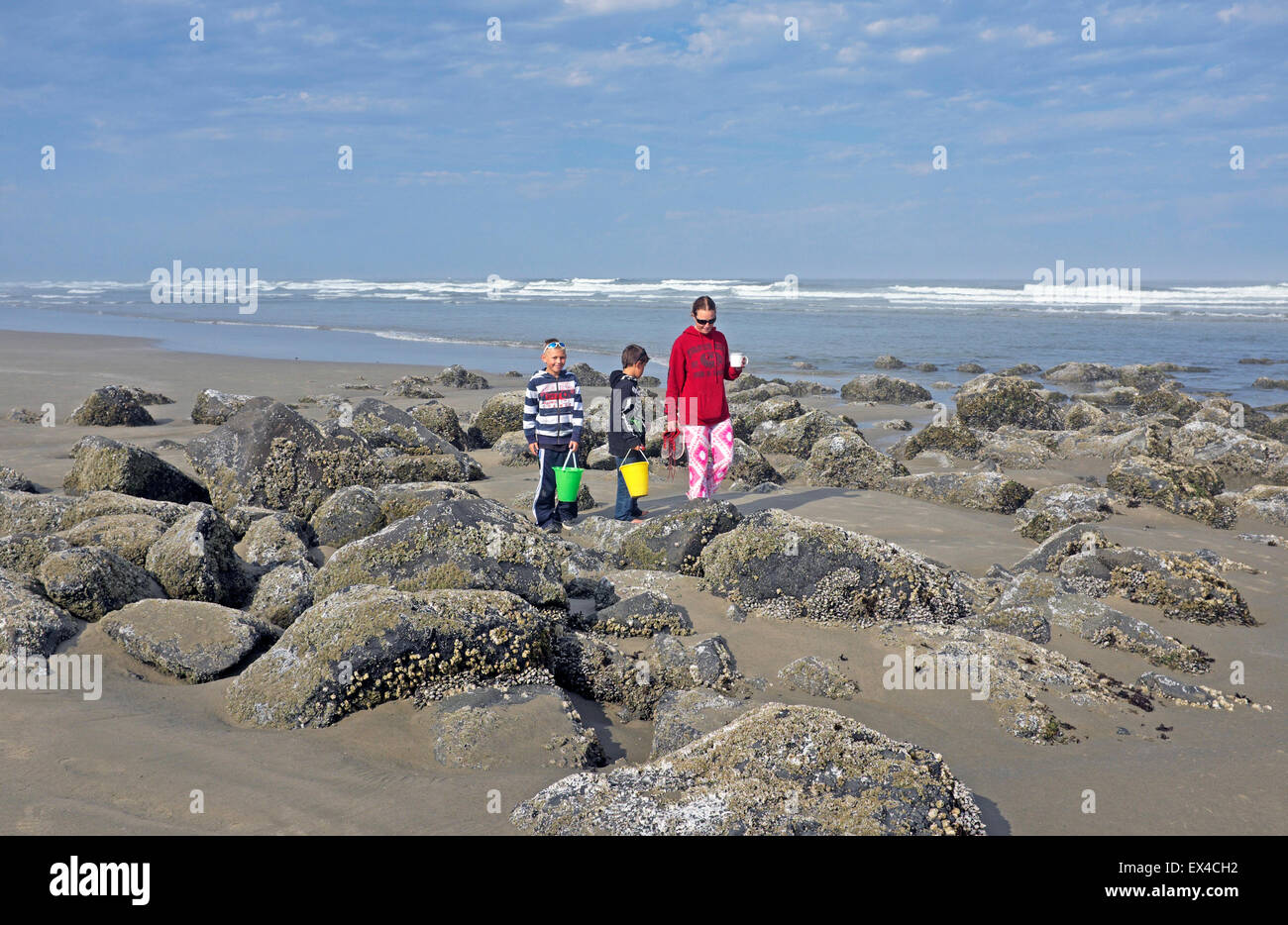 A mother and her two male children wander a tide pool looking for shells near Newport, Oregon - Stock Image