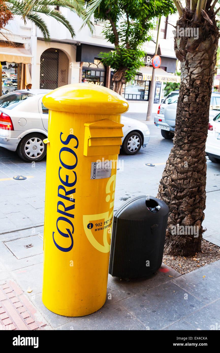 Spanish mailbox mail postbox post box correos Spain posting yellow - Stock Image