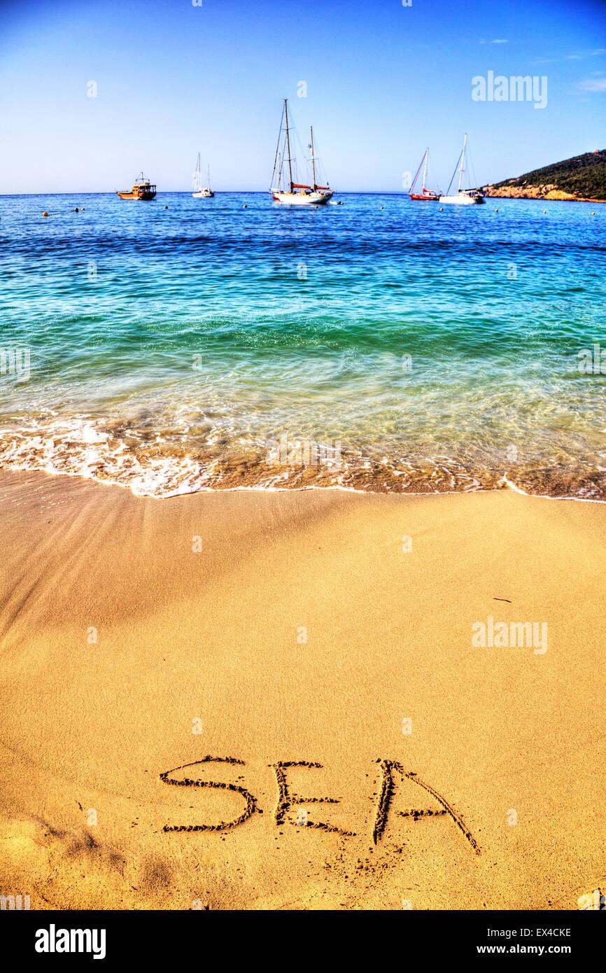 sea word in sand written on beach fun resort seas coast coastline holidays vacations trips trip getaway Ibiza Spain - Stock Image