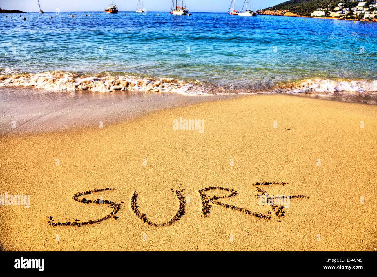 Surf word in sand written on beach Spanish fun resort seas coast coastlines holidays vacations trips trip getaway - Stock Image