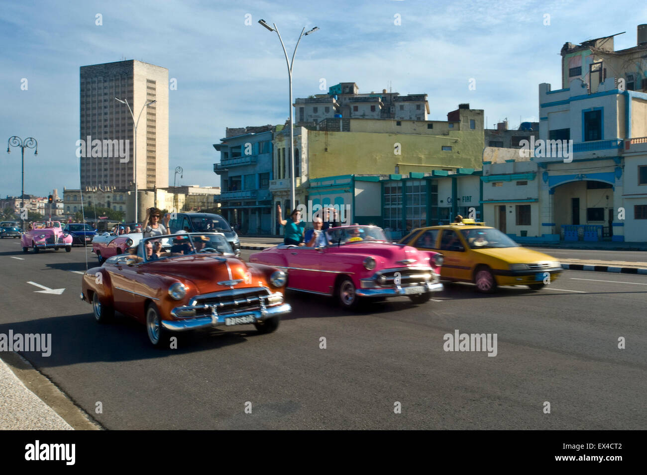 Horizontal view of classic old American cars driving along the Malecon in Havana, Cuba. - Stock Image