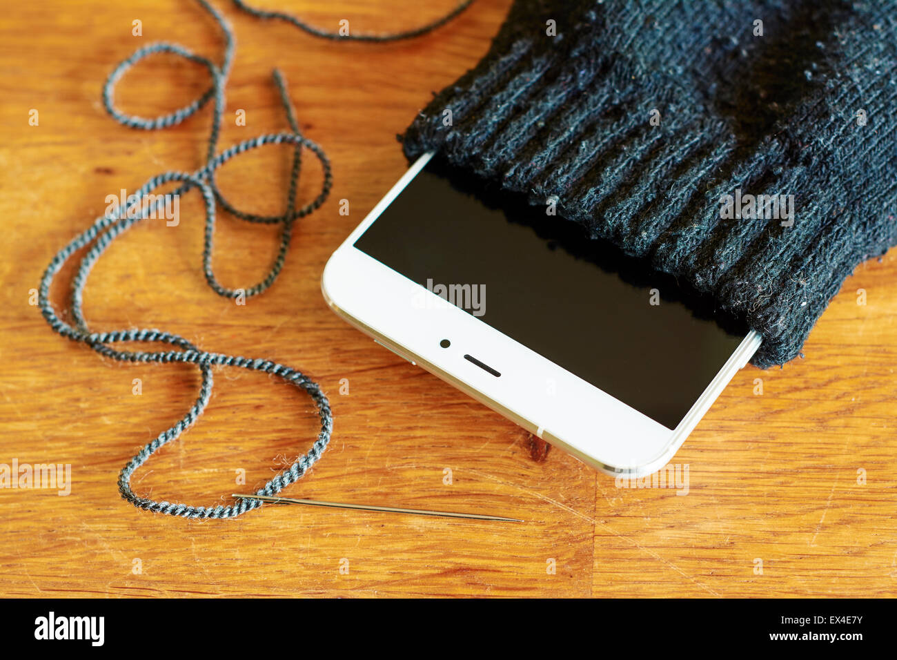 Old sock being reused as smartphone case. - Stock Image