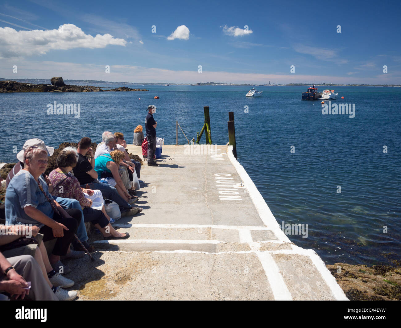 Holidaymakers on the Island of Herm, queuing for the ferry to Guernsey - Stock Image