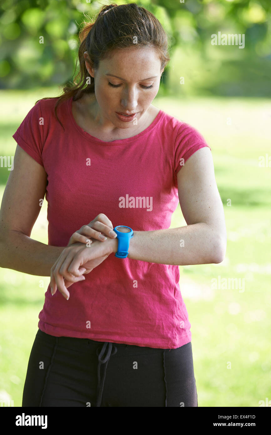 Female Runner In Park Checking Time Using Stopwatch - Stock Image