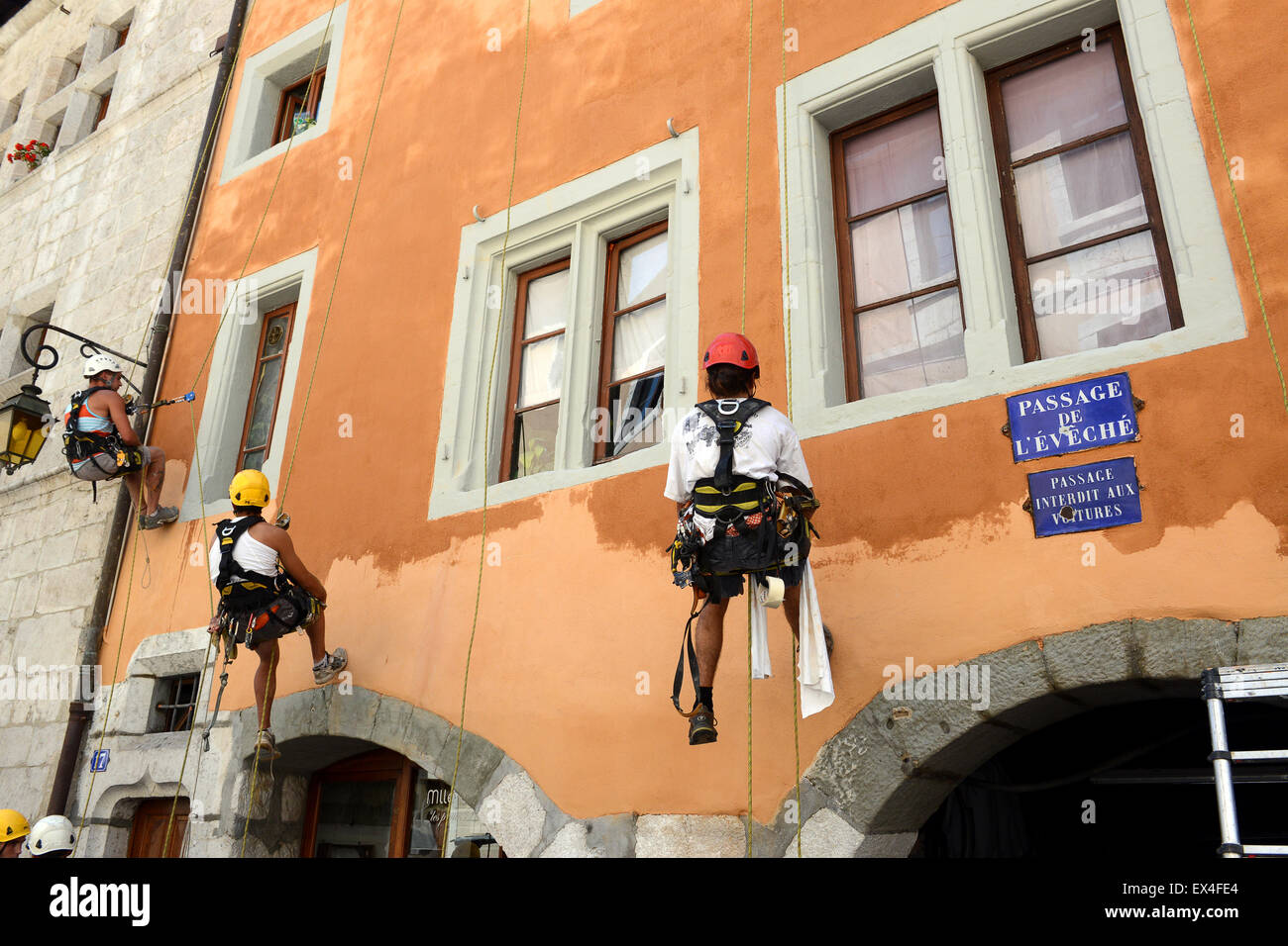 Painter painters suspended on ropes with abseil climbing harness painting the external wall of a building in Annecy - Stock Image