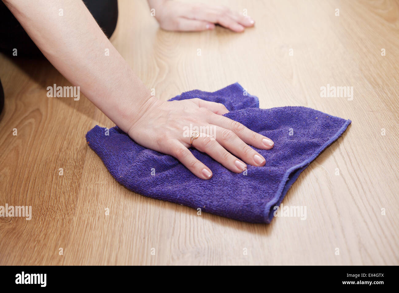 woman's hand cleaning the wooden floor with a blue cloth closeup Stock Photo