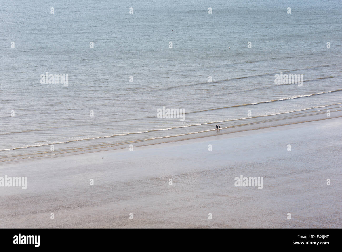 Two people on a deserted beach, Rhossili, Gower, South Wales - Stock Image