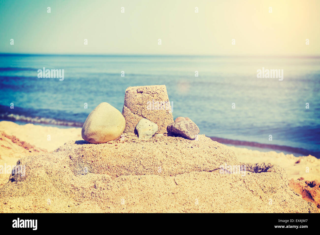 Vintage retro toned simple sandcastle on a beach, summer holidays concept. - Stock Image