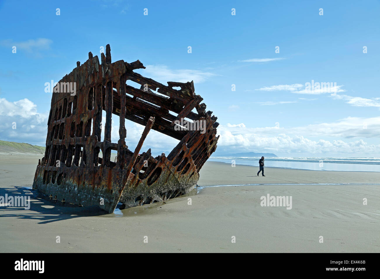 Tourist at shipwreck of the Peter Iredale ship, Fort Stevens State Park, near Astoria, Oregon USA - Stock Image
