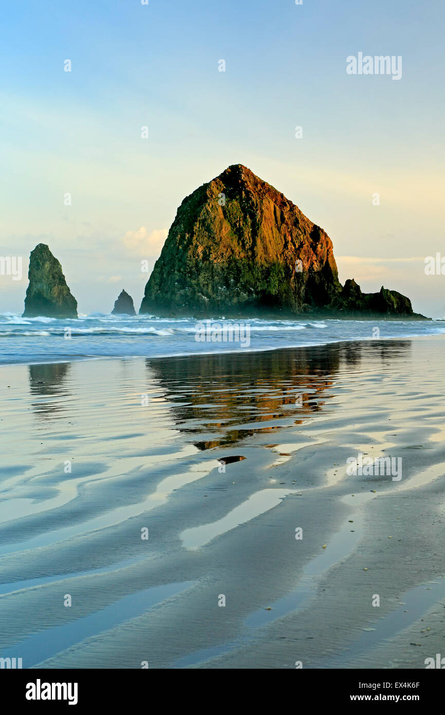 Haystack Rock reflected on water and ripples, Cannon Beach, Oregon USA - Stock Image