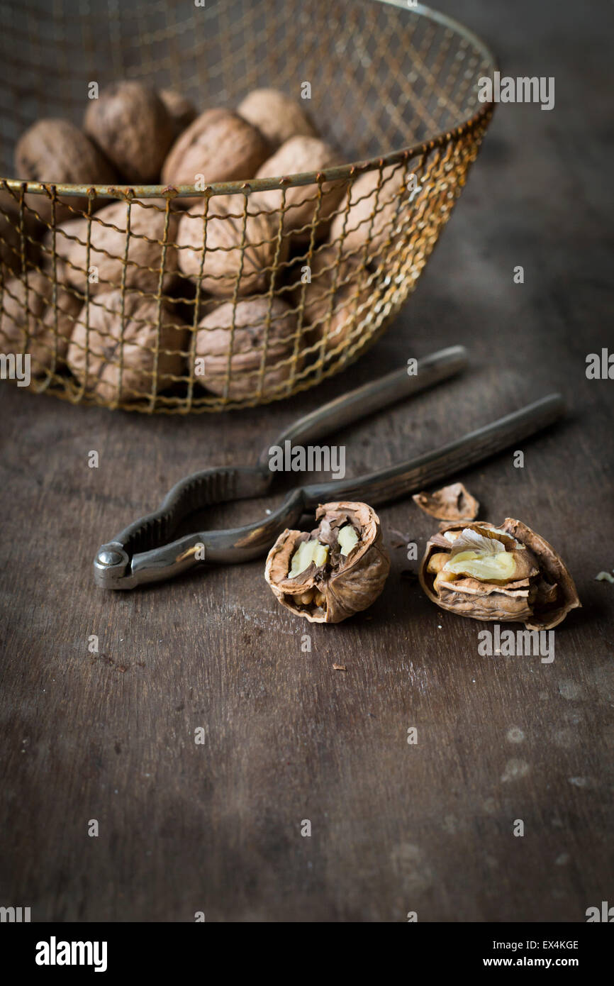 Walnuts in vintage wire basket on wooden table Stock Photo