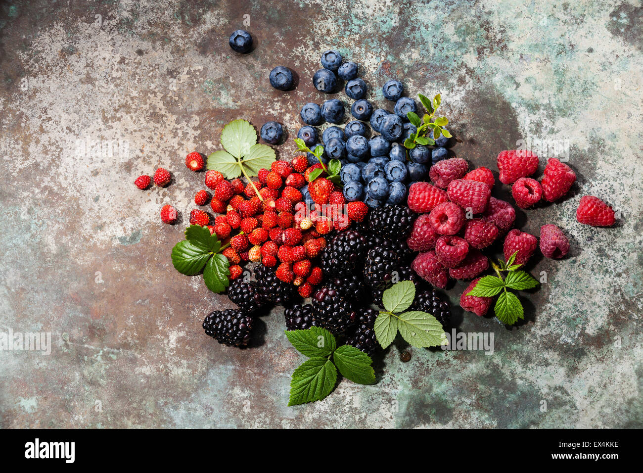 Assorted fresh berries with leaves on metal background - Stock Image