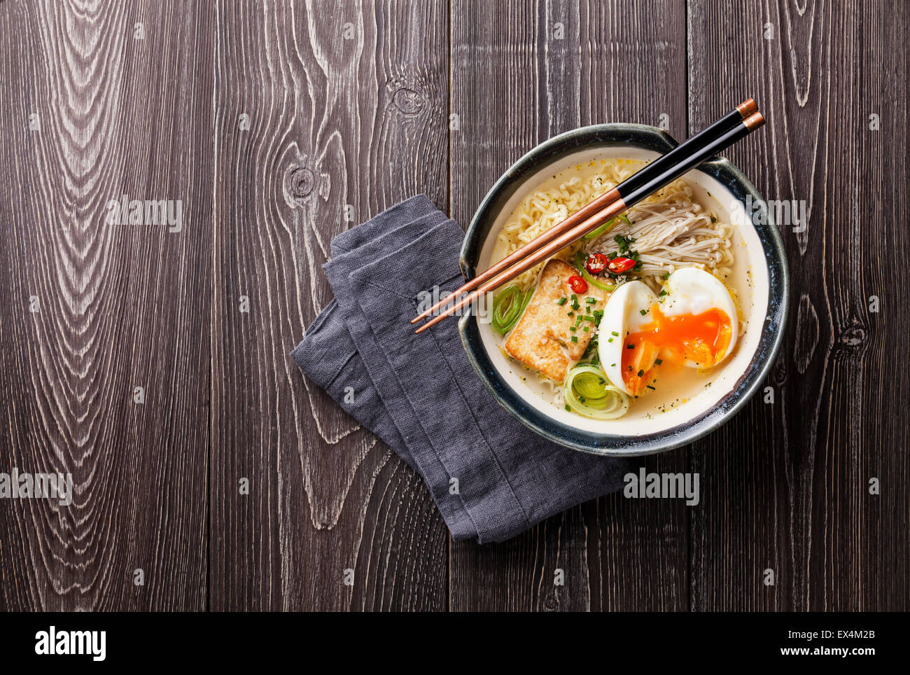 Chinese noodles with egg, tofu and enoki in bowl on gray wooden background - Stock Image