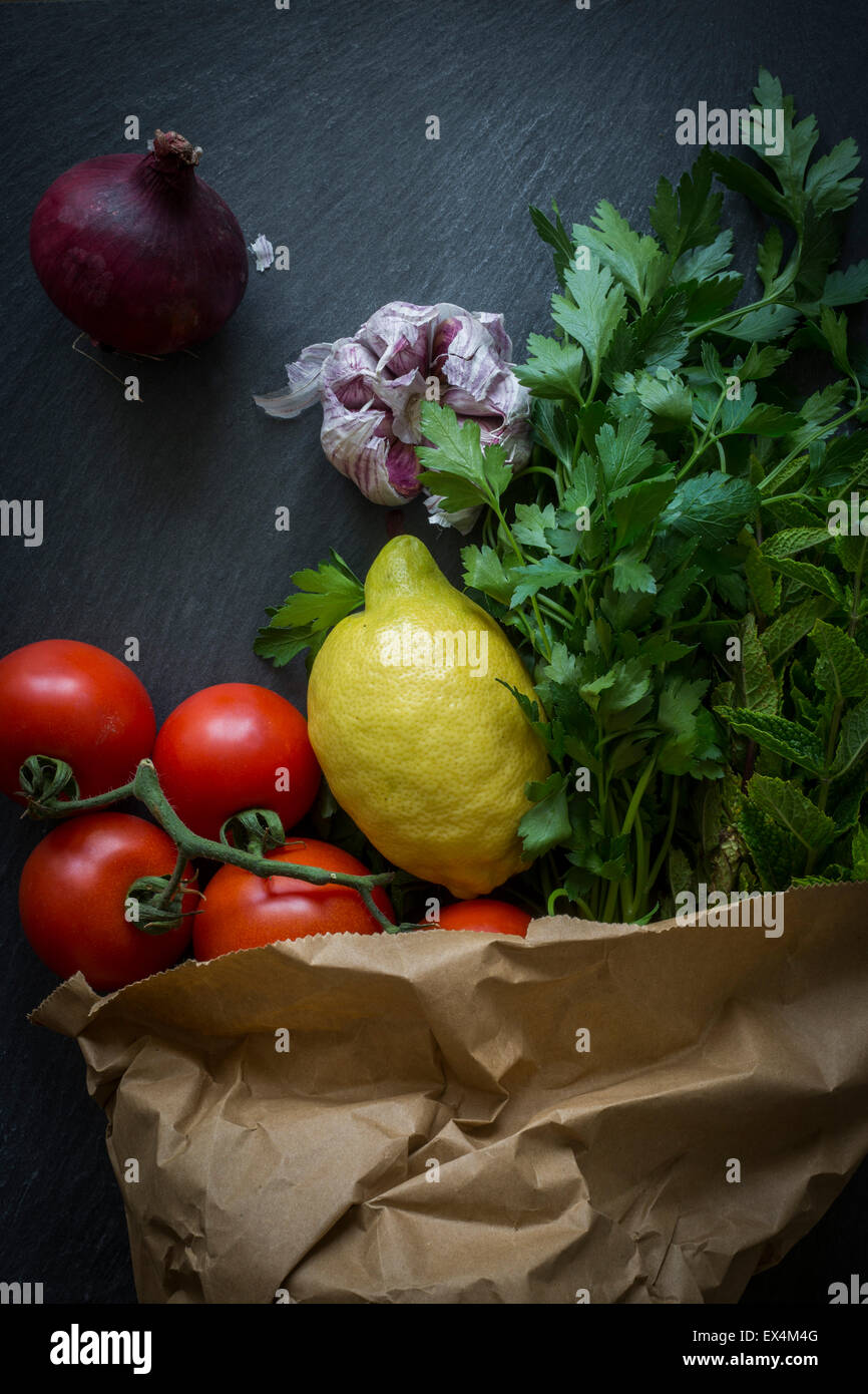 Vegetables in paper bag fresh from the market on slate background: Top view - Stock Image