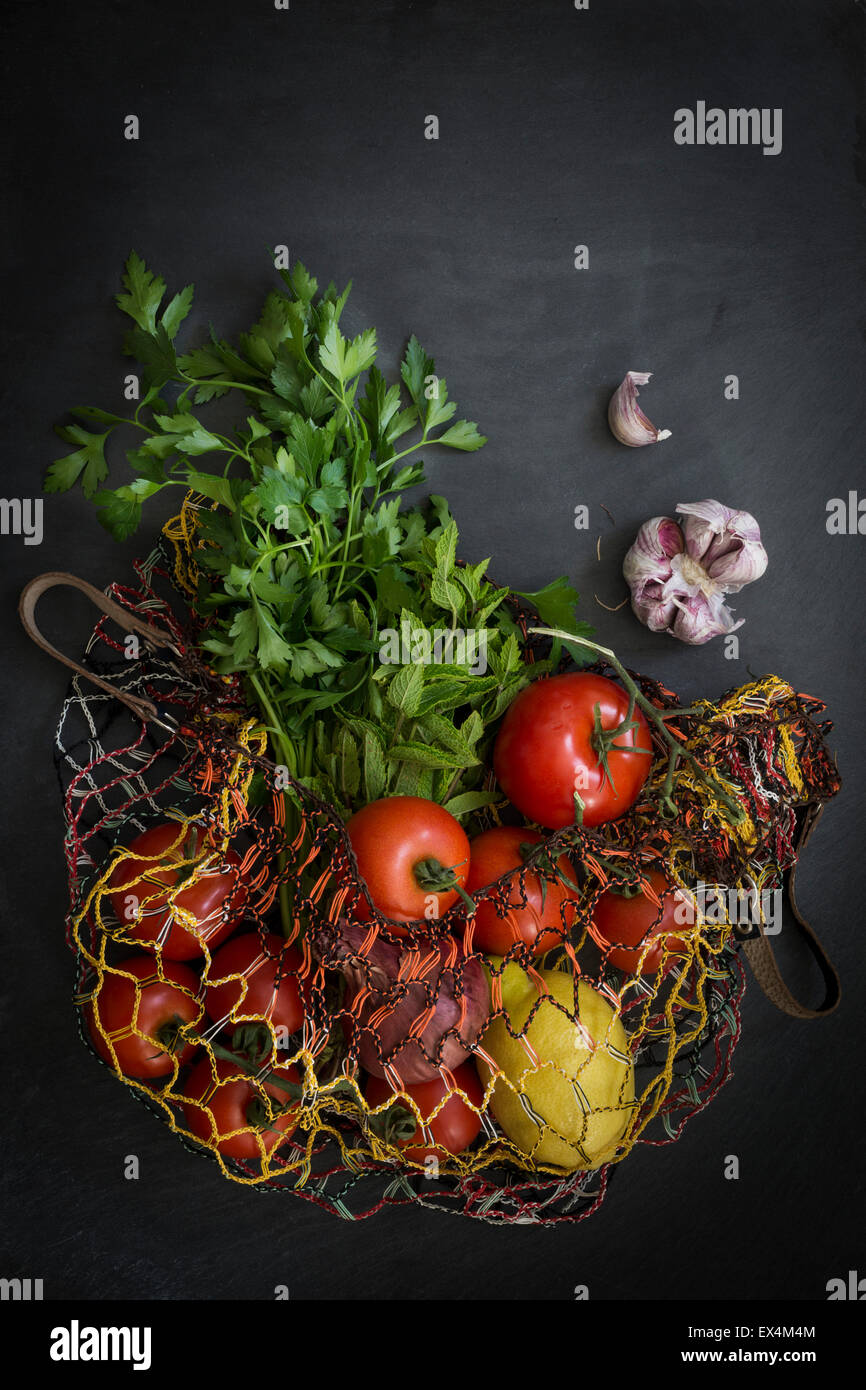 Vegetables in string bag fresh from the market on slate background: Top view - Stock Image