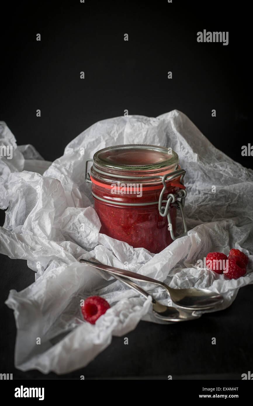 Jar of raw raspberry & chia jam in white paper before dark background Stock Photo