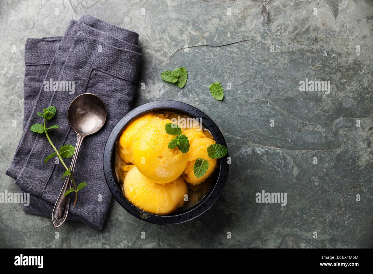 Mango ice cream sorbet with mint leaves on stone slate background - Stock Image