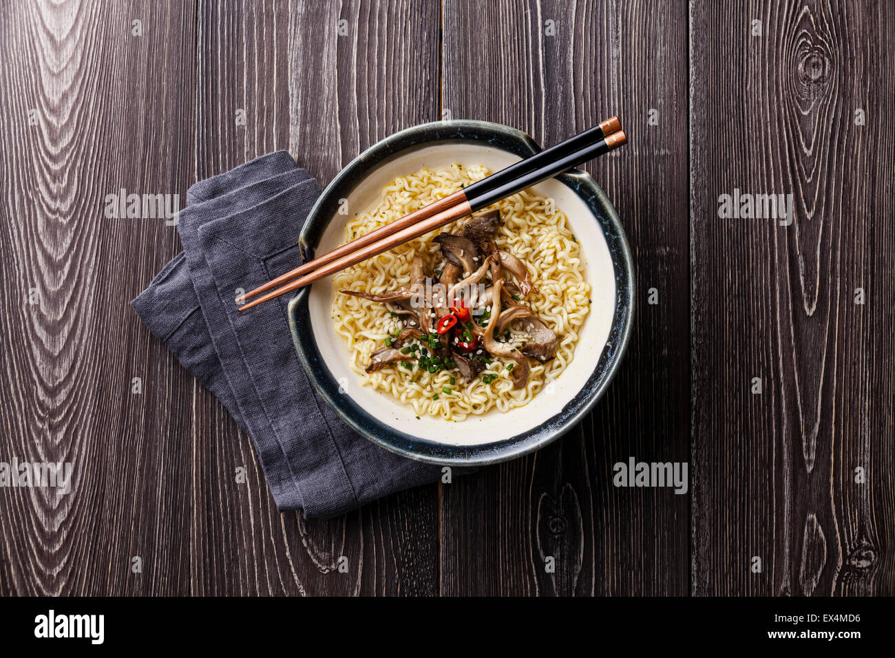 Asian noodles with Oyster mushrooms in bowl on gray wooden background - Stock Image