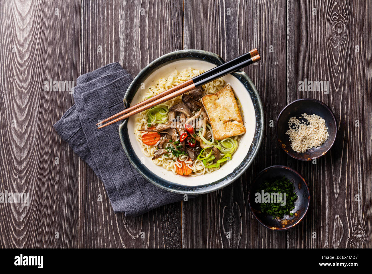 Asian noodles with tofu, oyster mushrooms and vegetables in bowl on gray wooden background - Stock Image