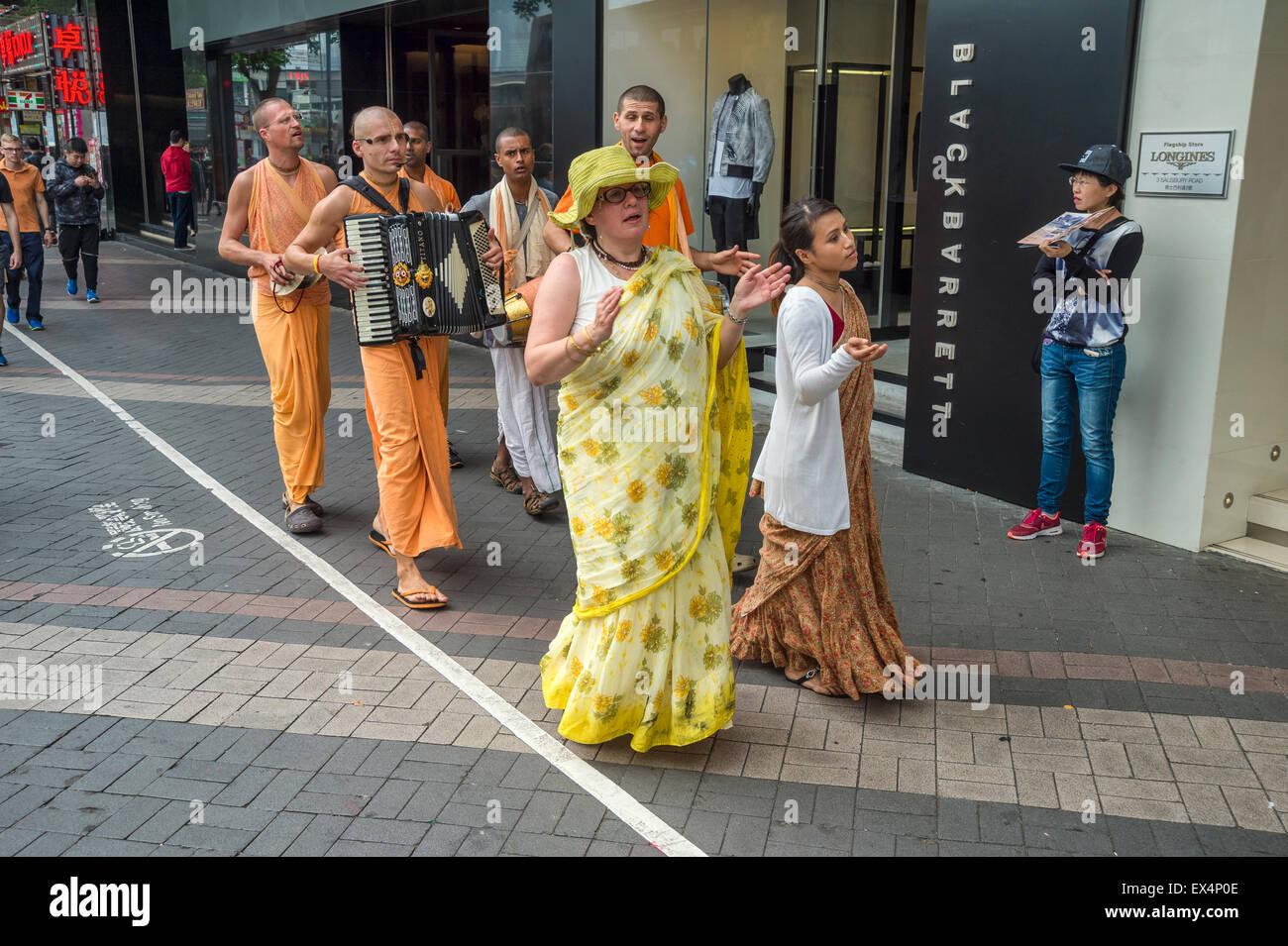 Devotees from Hare Krishna play music and sing on the street, in Hong Kong, China - Stock Image
