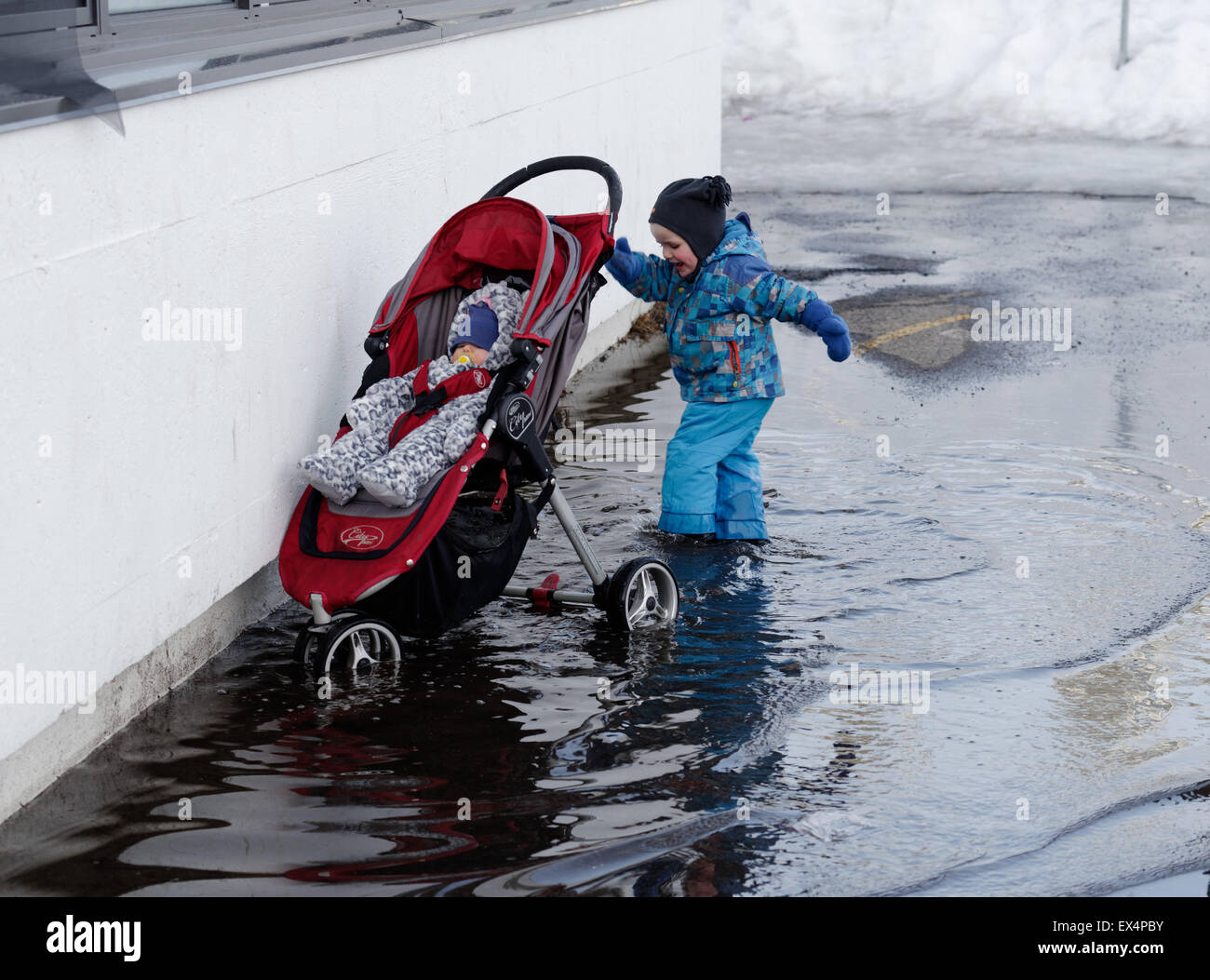 A little boy pushing a his baby sister's pushchair through a deep puddle Stock Photo