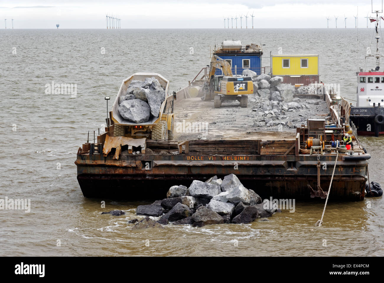A barge being used to make sea defences -  a lorry dumping huge boulders into the sea to make a breakwater. Clacton - Stock Image
