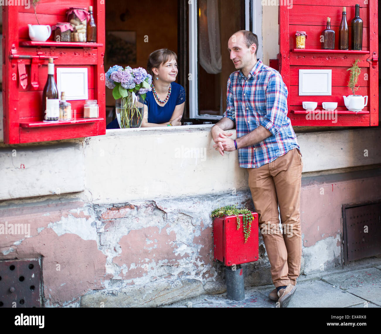 Happy young couple. A young woman looks out from the window of the house, and the man standing on the street talking - Stock Image