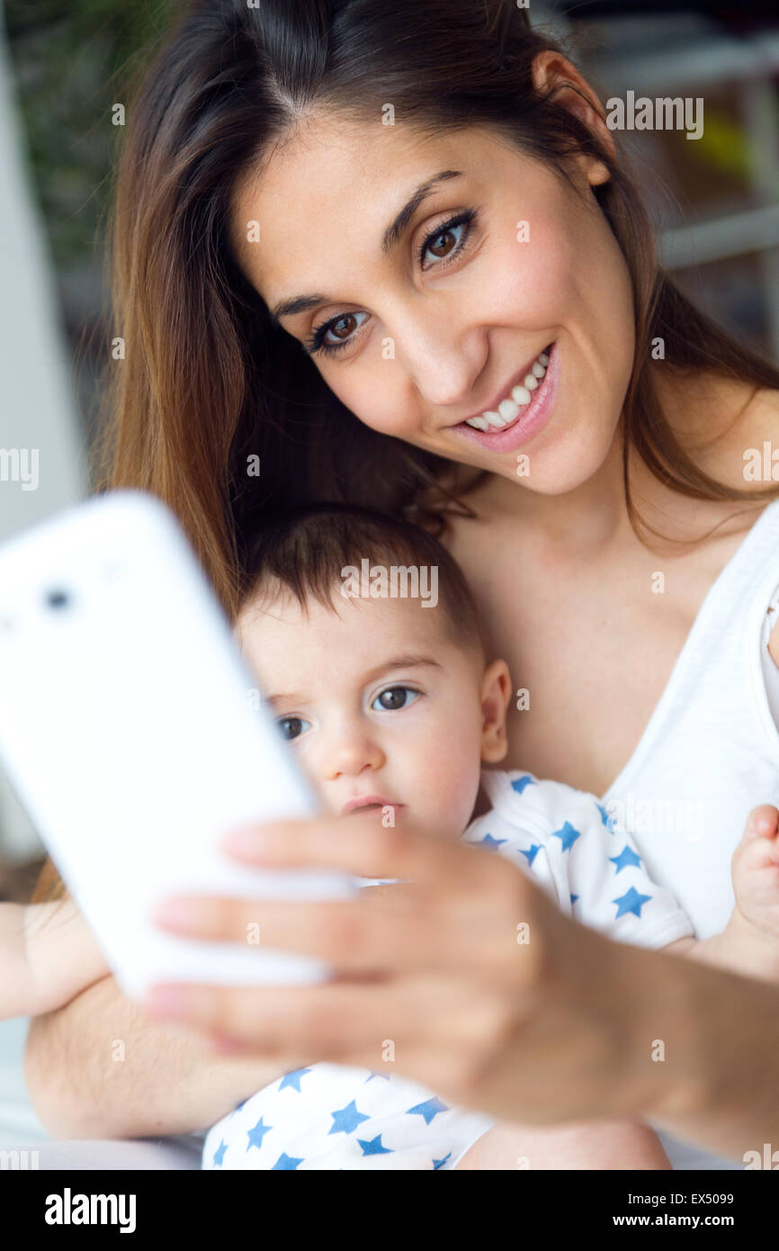Portrait of beautiful mother and baby taking a selfie at home. - Stock Image